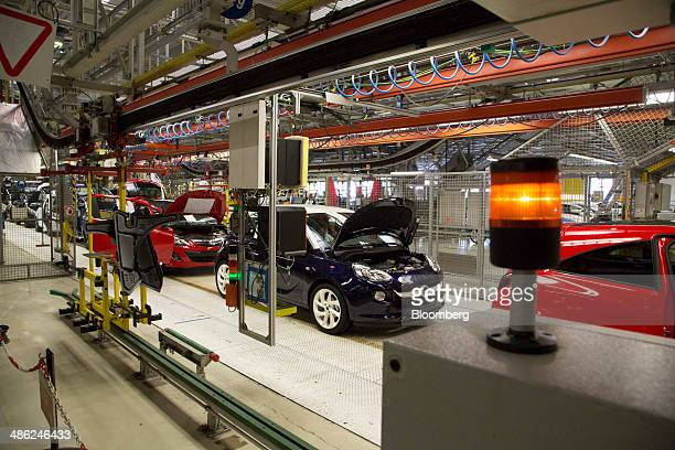 A blue Adam Opel AG center sits between red Opel Corsa automobiles on the production line at the Opel factory operated by General Motors Co in...