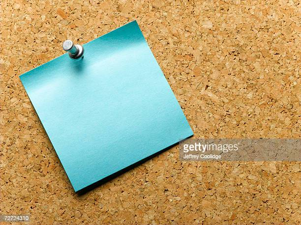 Blue adhesive note pinned to notice board, close-up
