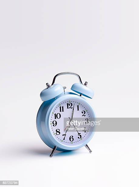 blue alarm clock on white background - alarm clock stock pictures, royalty-free photos & images