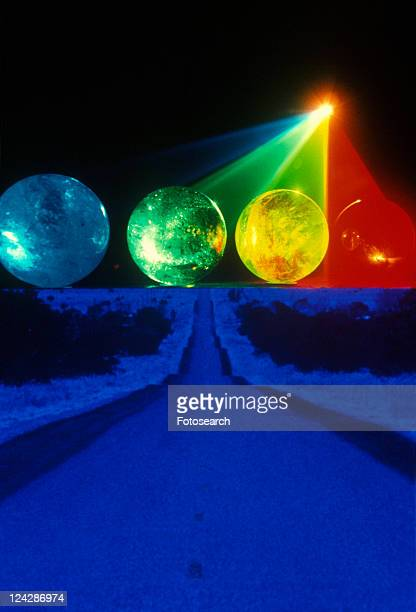 A blue and black horizon below several multi-colored spheres appearing as planets with laser lights shining through