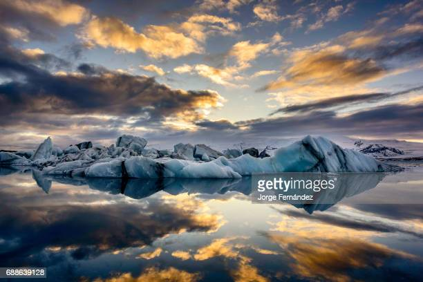 Blue and black icebergs floating on the Jokullsarlon glacial lagoon at sunset