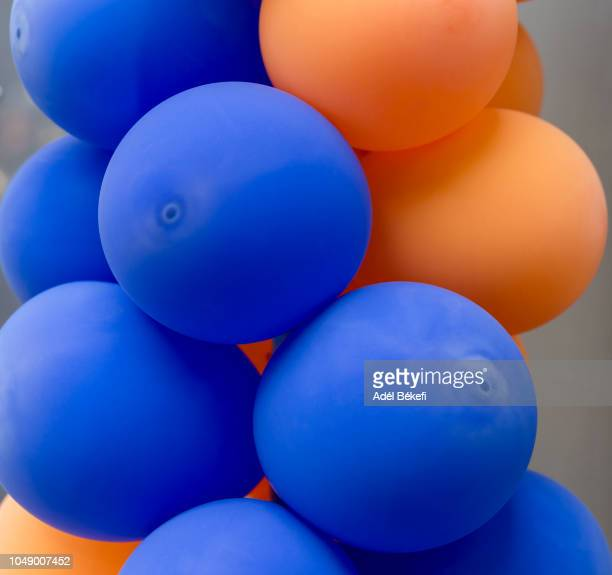 blue and orange balloons - latex stock pictures, royalty-free photos & images