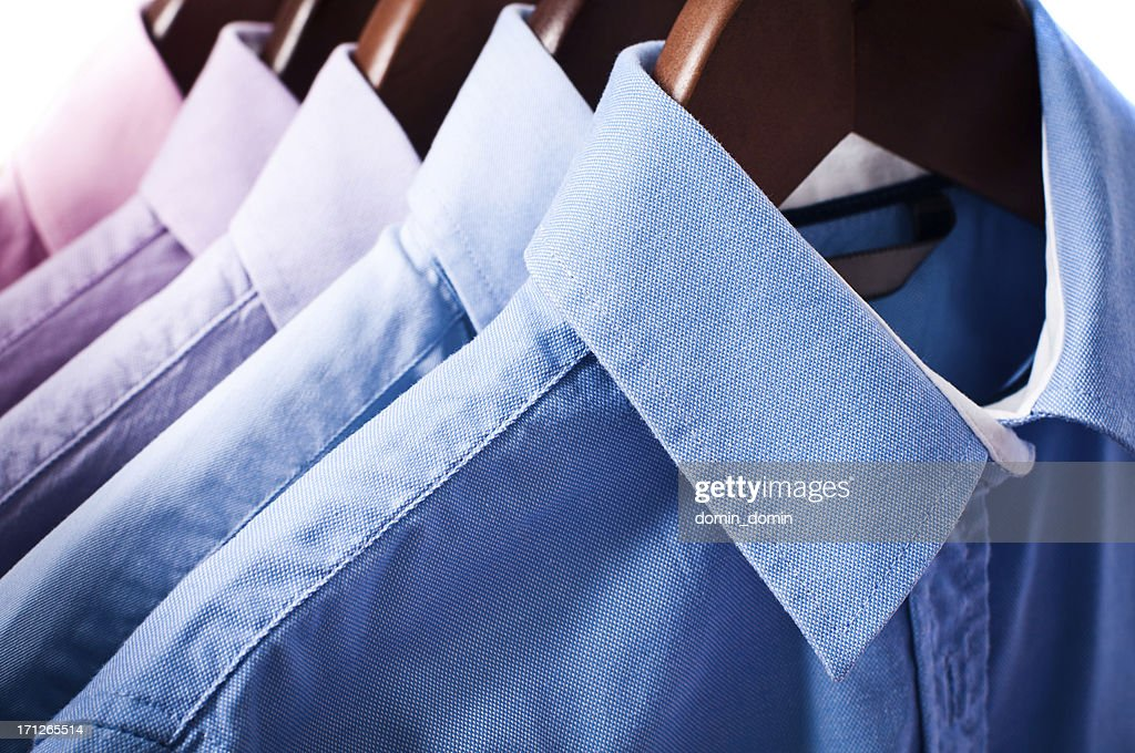 Blue and pink elegant button down shirts hanging on hangers : Stock Photo