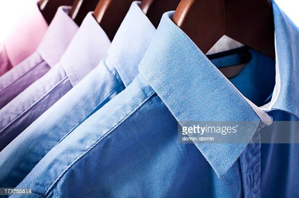 Blue and pink elegant button down shirts hanging on hangers