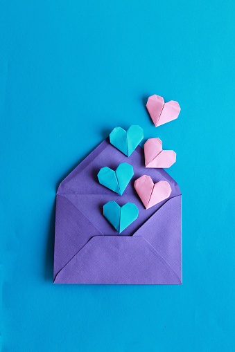Blue and pink paper hearts on the violet envelope - gettyimageskorea