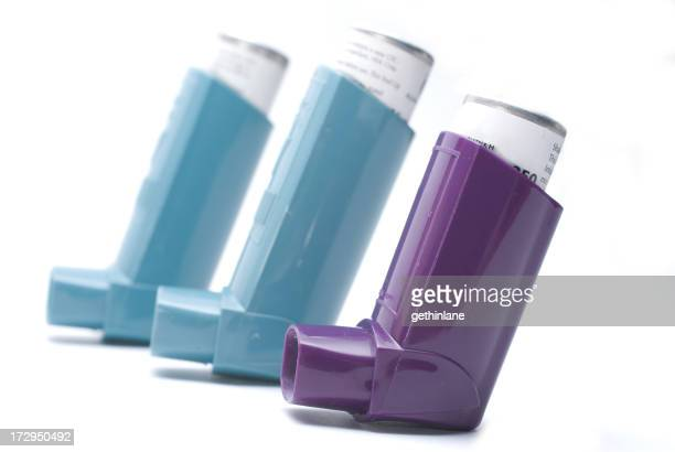 Blue and purple medicated inhalers on white background