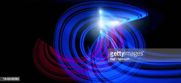 Blue and red light trails creating an abstract swirling wave pattern on black background