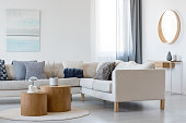 Blue and white abstract painting and mirror in wooden frame in elegant living room interior with corner sofa and coffee table