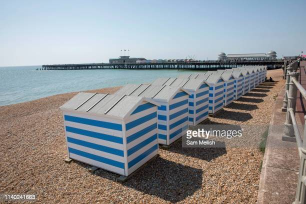 Blue and white beach huts along Hastings seafront on the 20th April 2019 in Hastings in the United Kingdom Hastings is a town on Englands southeast...