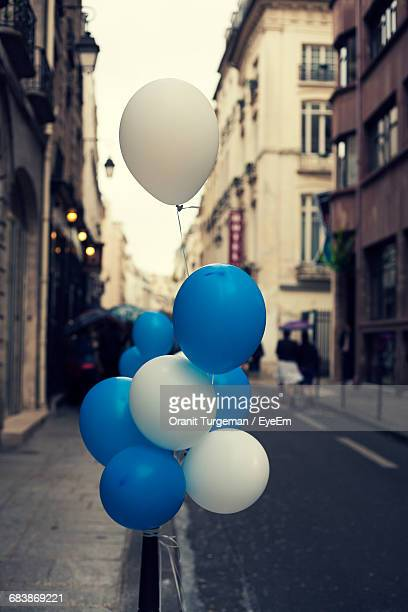 Blue And White Helium Balloons Tied To Bollard On Street In City