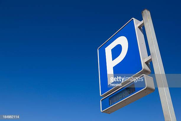 blue and white parking sign over blue sky - parking sign stock photos and pictures