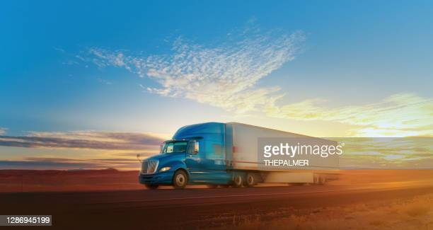 blue and white semi-truck speeding on a single lane road usa - american culture stock pictures, royalty-free photos & images