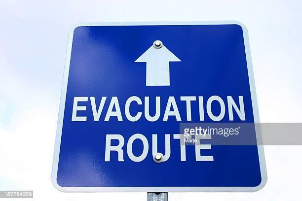 blue and white sign with evacuation route on and arrow - evacuation stock pictures, royalty-free photos & images