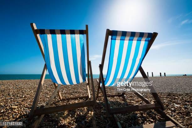 blue and white striped deck chairs and sun glare on the beach, brighton, uk - värmebölja bildbanksfoton och bilder