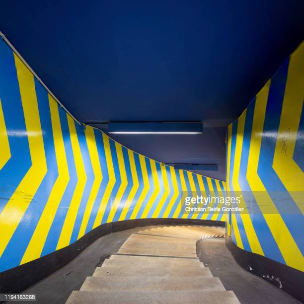 blue and yellow arrow signs in a staircase of the oez-subway station, munich, germany - christian beirle stock pictures, royalty-free photos & images