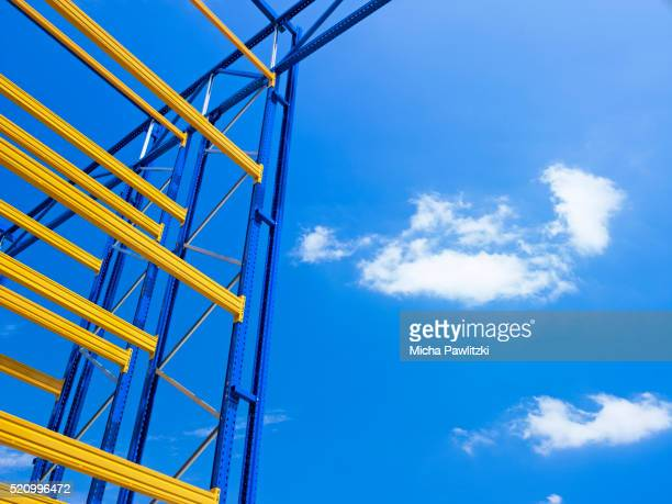 blue and yellow construction scaffold against blue sky - appearance stock pictures, royalty-free photos & images