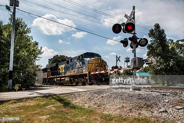 A Blue and Yellow Train is Coming Down the Track Railroad Train Crossing Sign With Arms Down and Red Lights Flashing a Warning That a Train is on the...