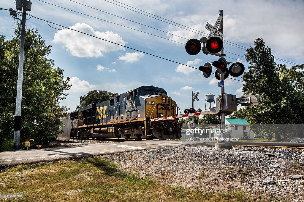 A Blue and Yellow Train is Coming Down the Track Railroad Train Crossing Sign With Arms : train track lights - azcodes.com