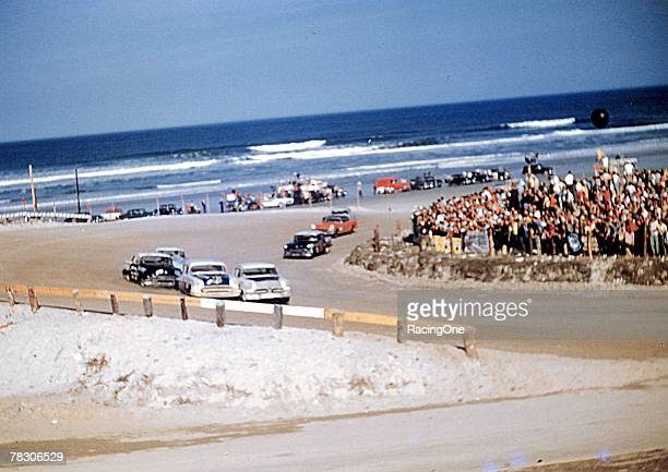 Blue Atlantic Ocean waves break on the shoreline as Grand National stock cars slam their way around the North Turn on Daytona's beach race course in...
