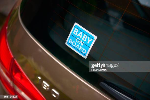 blue baby on board sticker in rear view window of car - fragile sticker stock pictures, royalty-free photos & images
