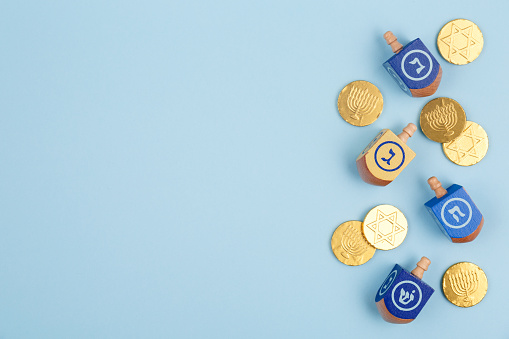 Blue background with multicolor dreidels and chocolate coins. Hanukkah and judaic holiday concept. 878751080