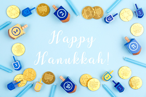 Blue background with multicolor dreidels, menora candles and chocolate coins with Happy Hanukkah wording. Hanukkah and judaic holiday concept. 1175747068