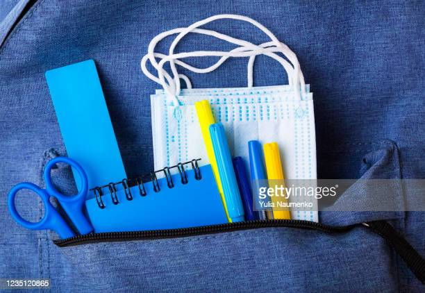 blue backpack with different stationery and study supplies and medical face masks. back to school concept. the concept of the teachers day. protection against coronavirus of schoolchildren and students. studying in the new reality pandemic. - open backpack stock pictures, royalty-free photos & images
