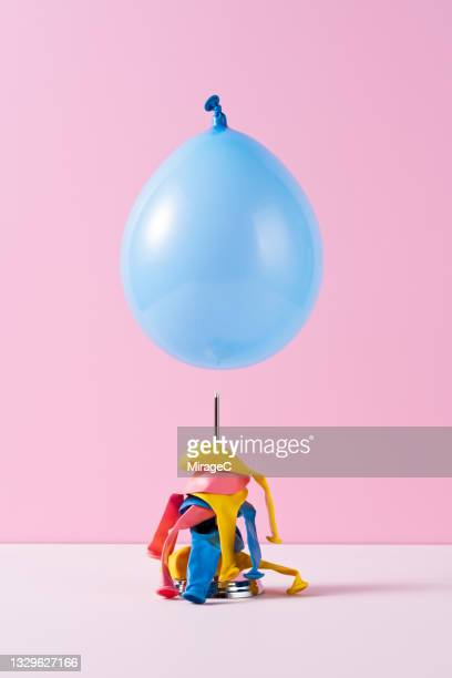 blue balloon about to fall on a spike - breekbaarheid stockfoto's en -beelden