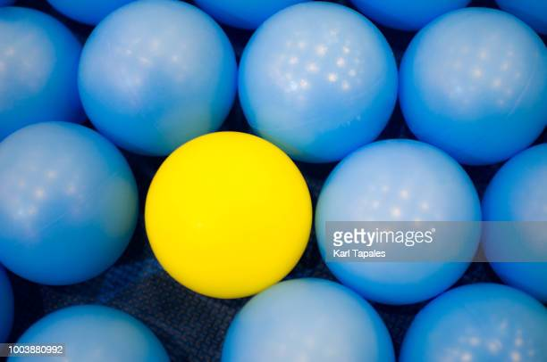 blue balls and one yellow ball - influencer photos stock photos and pictures