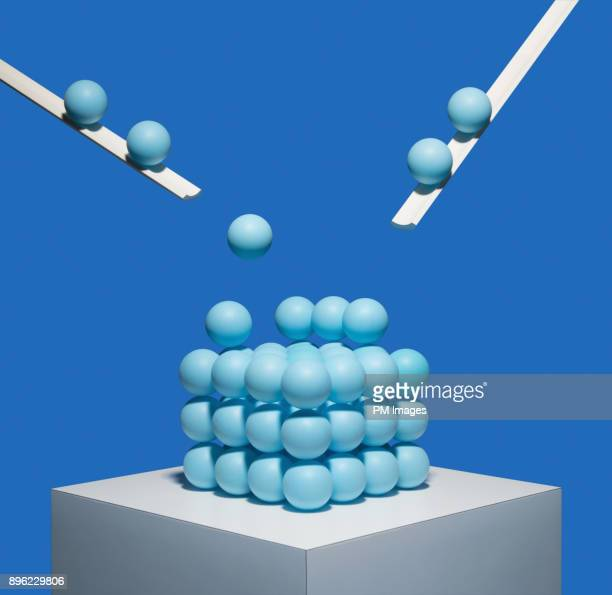 blue balls being deposited onto square pile - same action stock photos and pictures
