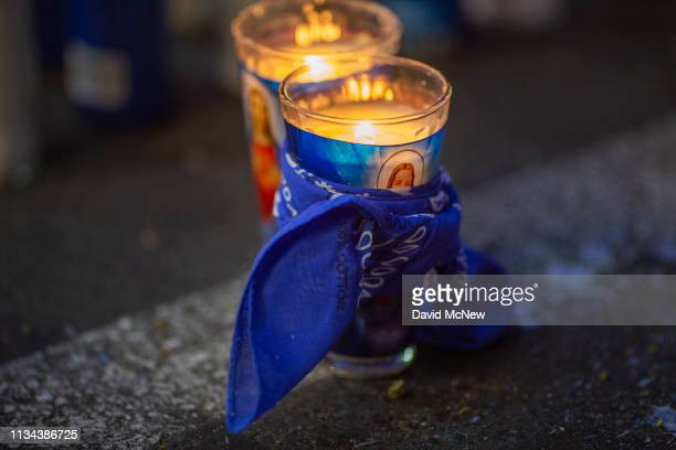 A blue bandana symbol of the Crips gang is seen in one of the makeshift memorials as people mourn the murder of Nipsey Hussle on April 1 2019 in Los...
