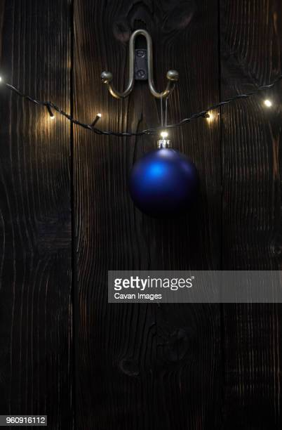 Blue bauble hanging by illuminated string lights on wooden wall during Christmas
