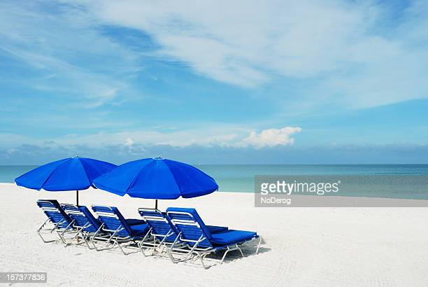 blue beach umbrellas on a white sandy beach. - marco island stock pictures, royalty-free photos & images