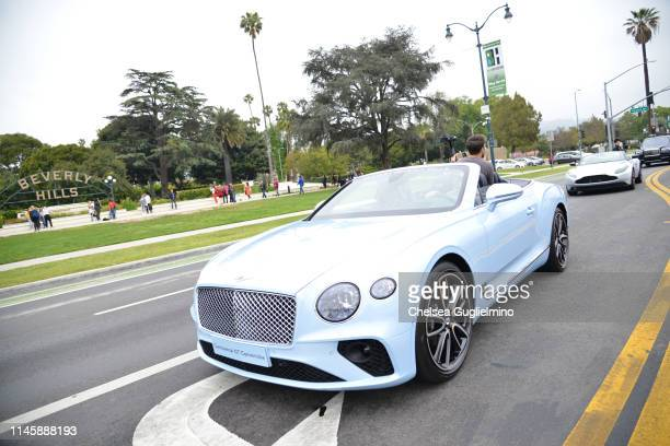 A blue Bentley Continental GT Convertible drives past Beverly Gardens Park at the 2019 BritWeek Car Rally on April 28 2019 in Beverly Hills California