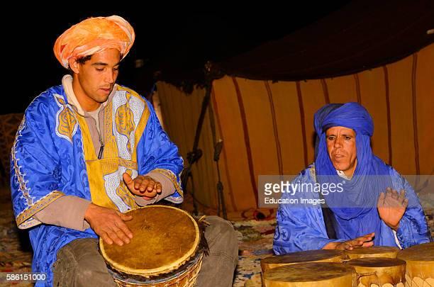 Blue Berber tuareg men playing djembe and bongo drums at night in Erg Chebbi desert Morocco