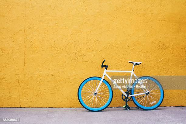 blue bicycle against yellow wall - bicycle stock pictures, royalty-free photos & images