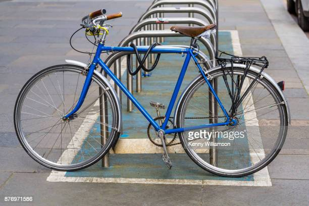 a blue bicycle - bicycle parking station stock photos and pictures