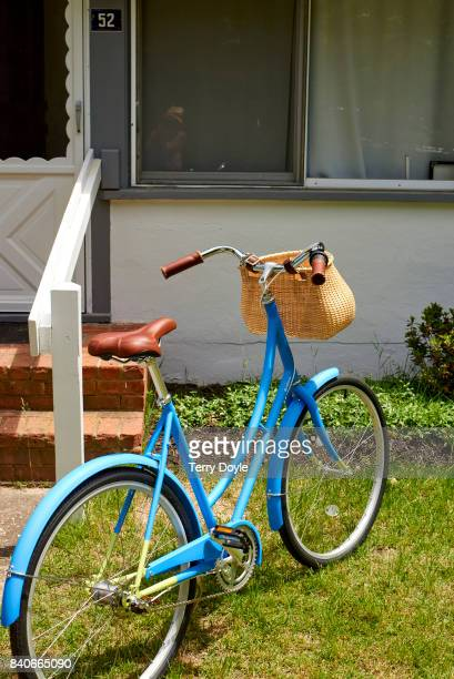 blue bicycle sitting outside a white house
