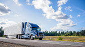 Blue big rig semi truck with grille guard trabsporting frozen cargo in refrigerator semi trailer with skirt spoiler running on the straight road