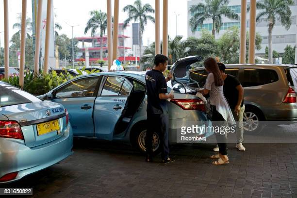 Blue Bird taxi driver looks on as passengers load their belongings into the trunk in Jakarta Indonesia on Sunday Aug 13 2017 PresidentJokoWidodois...