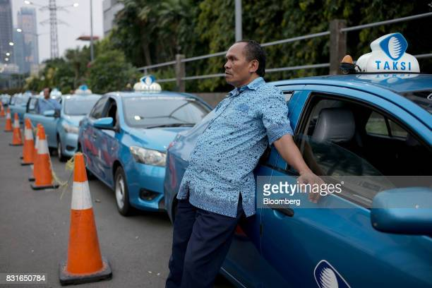 Blue Bird taxi driver waits for a fare in Jakarta Indonesia on Sunday Aug 13 2017 PresidentJokoWidodois seeking hundreds of billions of dollars to...