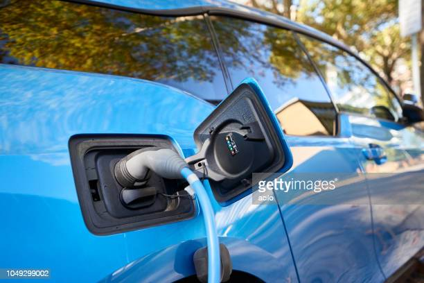 blue bmw i3 electric car plugged into charge - bmw stock pictures, royalty-free photos & images