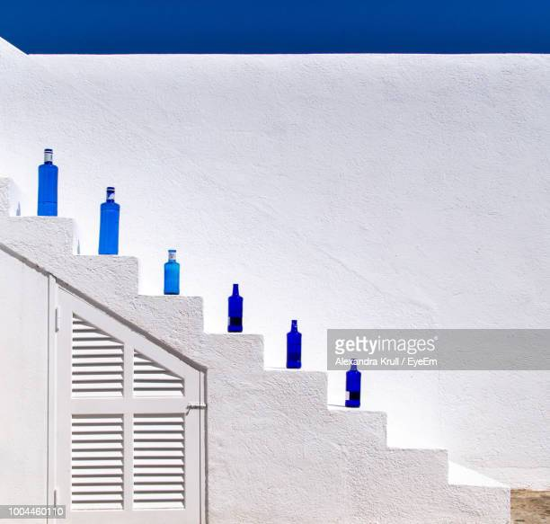 Blue Bottles On Staircase Against White Wall