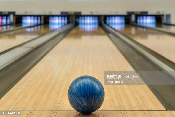 blue bowling ball on the track in the bowling center. - bowling stock pictures, royalty-free photos & images