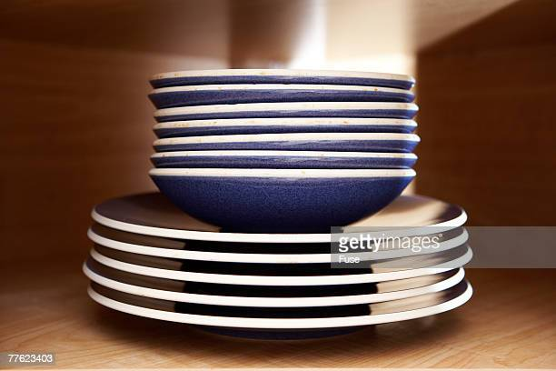 Blue Bowls and Plates Stacked in Cabinet