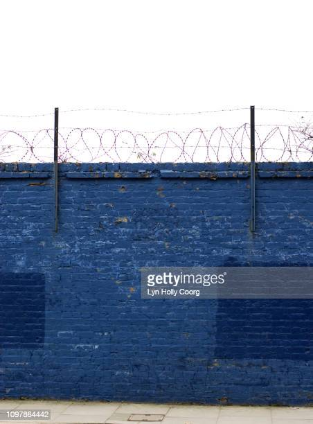 blue brick wall with barbed wire and sky - lyn holly coorg photos et images de collection