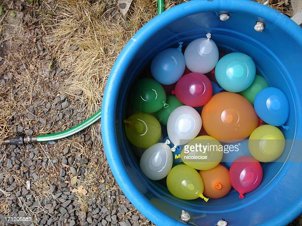 A blue bucket of filled water balloons on a gravel surface