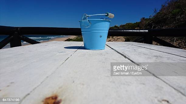 Blue Bucket On Wooden Table At Beach Against Clear Sky