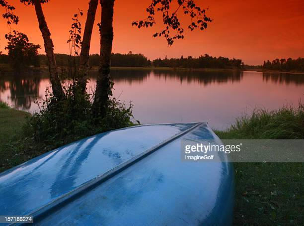 blue canoe and beautiful sunset on the lake - kenora stock pictures, royalty-free photos & images