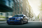 Blue car BMW E90 fast speed drive on city road